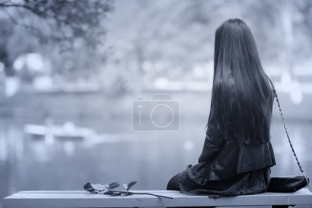 Photo for Monochrome black and white  portrait of a lonely girl sitting on the bench near the river - Royalty Free Image