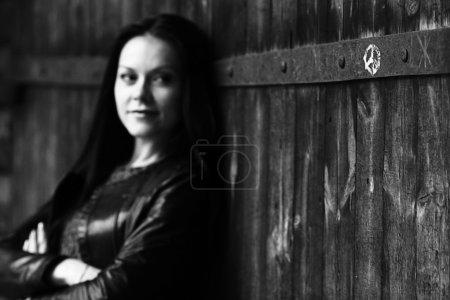 Photo pour Monochrome portrait noir et blanc d'une jeune fille près de la paroi en bois - image libre de droit