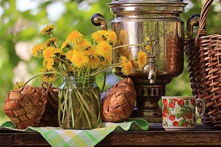 Samovar and dandelion flowers