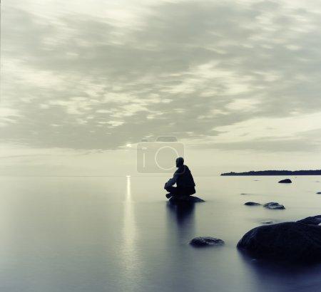 Man meditates on the lake, sitting on stone...