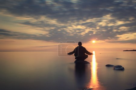 Man meditates on the lake