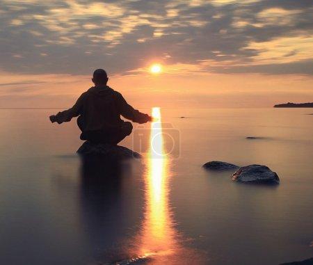 Man meditates on the lake during sunset...