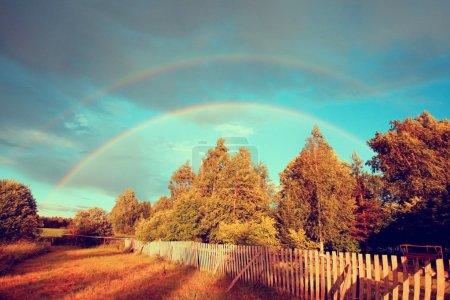 Rainbow over autumn forest