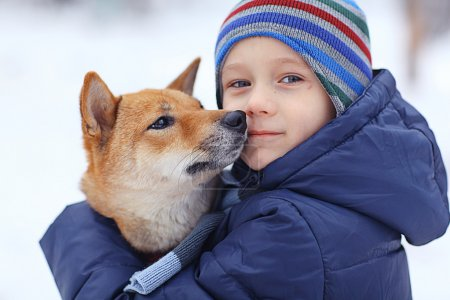 Little boy and dog in winter