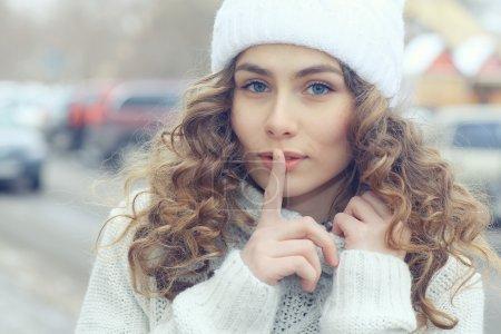 Photo pour Portrait de belle fille blonde en hiver à l'extérieur montrant signe de silence - image libre de droit