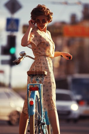girl  with a bicycle on the street