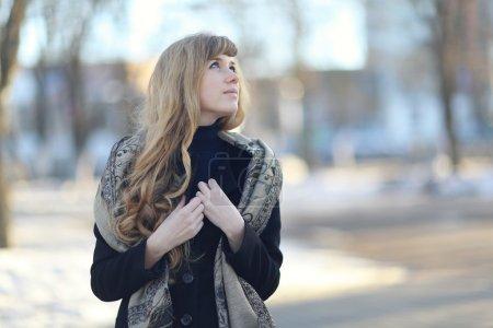 Photo pour Portrait d'une jeune fille aux longs cheveux blonds en manteau et écharpe à l'extérieur au printemps - image libre de droit
