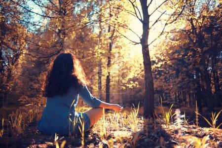 Photo pour Jeune fille méditer dans la forêt de l'été pendant le coucher du soleil - image libre de droit