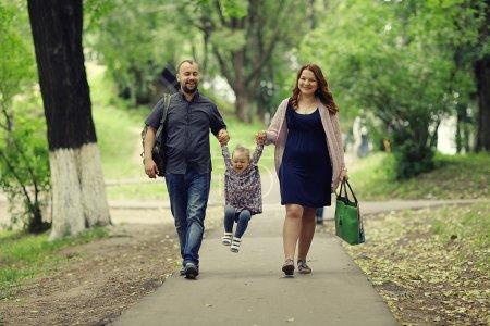 Photo pour Maman et jeune fille papa et maman, une jeune famille sur une promenade dans le parc en été - image libre de droit