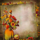Ackground with a bouquet of autumn leaves and berries in a vase from pumpkin