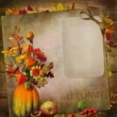 Vintage háttér, az őszi levelek a vázában tök kártyával