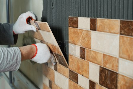 Photo for Laying Ceramic Tiles. Tiler placing ceramic wall tile in position over adhesive - Royalty Free Image