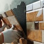 Laying Ceramic Tiles. Tiler placing ceramic wall t...