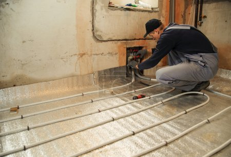 Man working installer connects the underfloor heat...