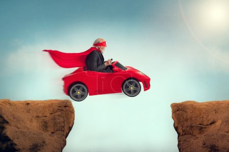 Senior superhero driving a car off a ravine