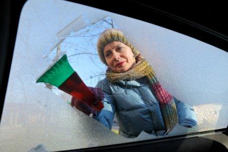 Photo pour Scène d'hiver, femme adulte raclant la glace du pare-brise de la voiture - image libre de droit
