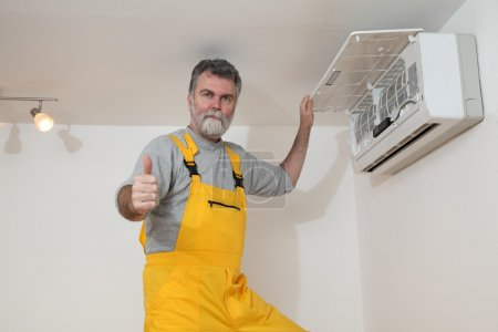 Photo for Electrician examine or install air condition device, gesturing with thumb up - Royalty Free Image