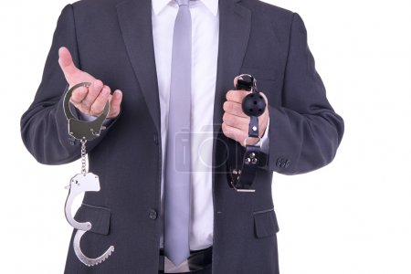 Businessman holding handcuffs and ball gag.