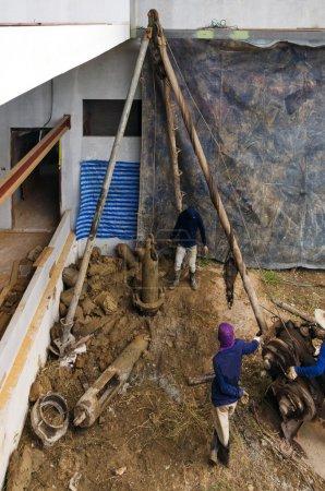 Photo pour Travailleurs forant pour une pile de fondation sur le chantier de construction - image libre de droit