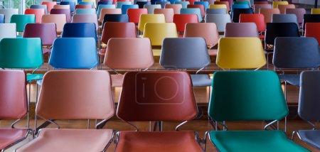 Photo pour Rangées de chaises colorées dans l'auditorium - image libre de droit