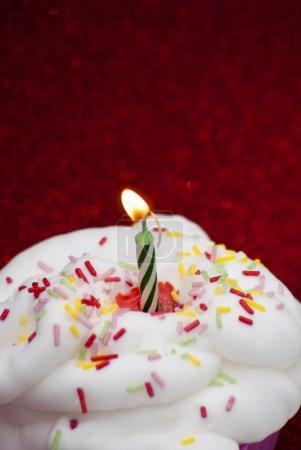 Photo pour Petit gâteau avec une bougie allumée sur fond rouge vif - image libre de droit