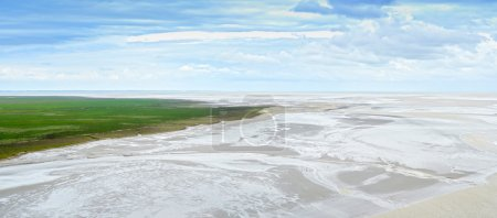 Low tide in Mont Saint Michel Bay. Panorama in Normandy, France.