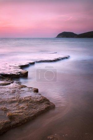 Baratti bay, headland hill, rocks and sea on sunset. Tuscany, It