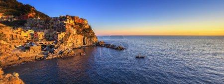 Manarola village panorama, rocks and sea at sunset. Cinque Terre