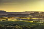 Tuscany spring, rolling hills on sunset. Rural landscape. Green