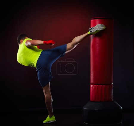 Photo for Young man exercising bag boxing in studio - Royalty Free Image