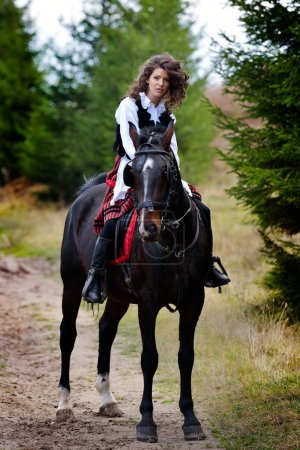 young woman riding horse outdoor