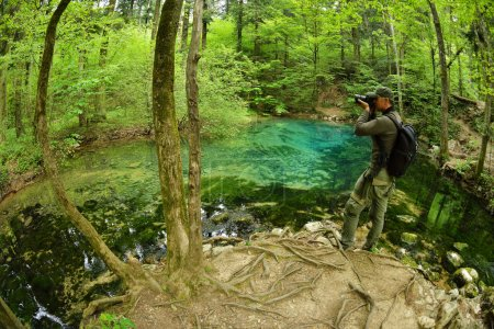 photographer visiting beautiful pond in the woods