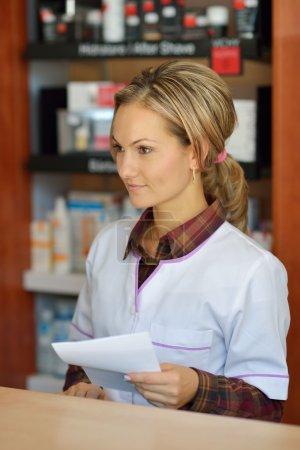 female pharmacist holding prescription