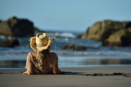 young woman sitting on the beach in summer vacation