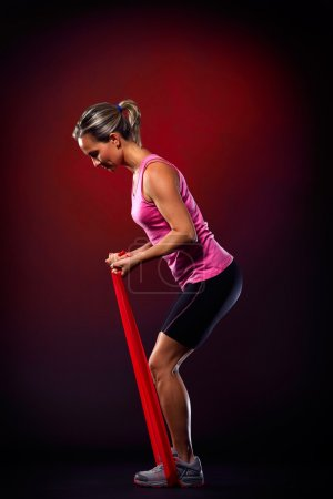 young woman exercising with elastic fitness band