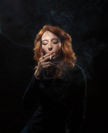 Photo pour Portrait d'une belle femme qui fume sur un fond noir. - image libre de droit