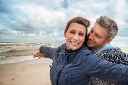 Photo pour Petit ami insouciant avec petite amie sur la côte venteuse - image libre de droit