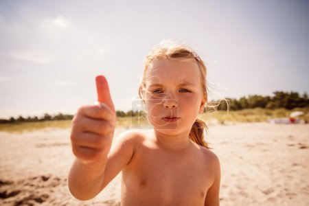 Photo for Child looking camera with finger up - Royalty Free Image