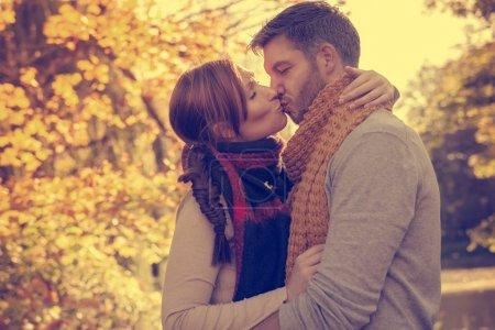 Photo pour Heureux embrasser automne couple saisonnier - image libre de droit