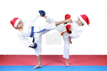 Girl and boy in caps of Santa Claus are beating kick leg
