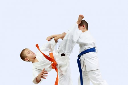 The athlete with the orange belt beats athlete with a blue belt blow leg on the head