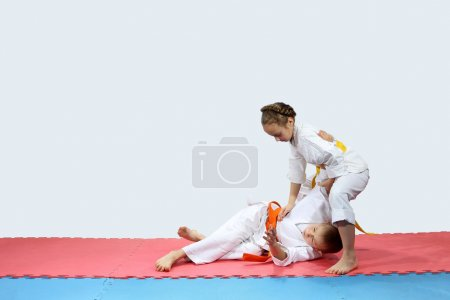 On the red and blue mat boy and girl in karategi are training throwing