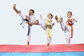 Tři děti v karategi bili kop nohou vpřed