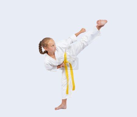 On a light background sportswoman beats blow leg