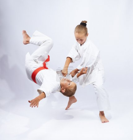 The girl in judogi throws the boy