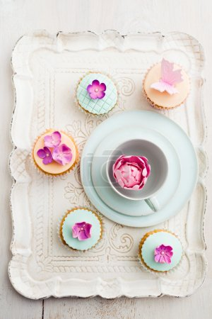 Cupcakes decorated with pink sugar flowers and a s...