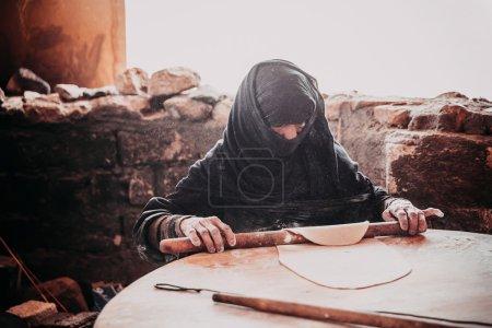 Old Arab woman prepares bread