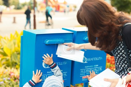 Kids helps her mother to puts letters in the mailbox