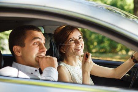 Foto de Gritos del esposo hasta su esposa aplicar lápiz labial en el espejo retrovisor el vehículo en movimiento. - Imagen libre de derechos