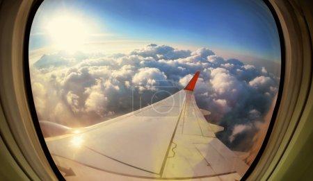 Photo pour Nuages et ciel vus à travers la fenêtre d'un aéronef - image libre de droit